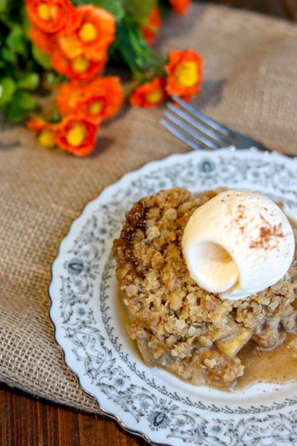 Apple Crisp with a scoop of vanilla icecream and some orange flowers on a burlap sack