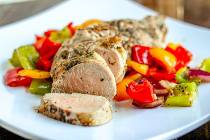 Sliced roasted pork tenderloin with vegetables on white serving plate.