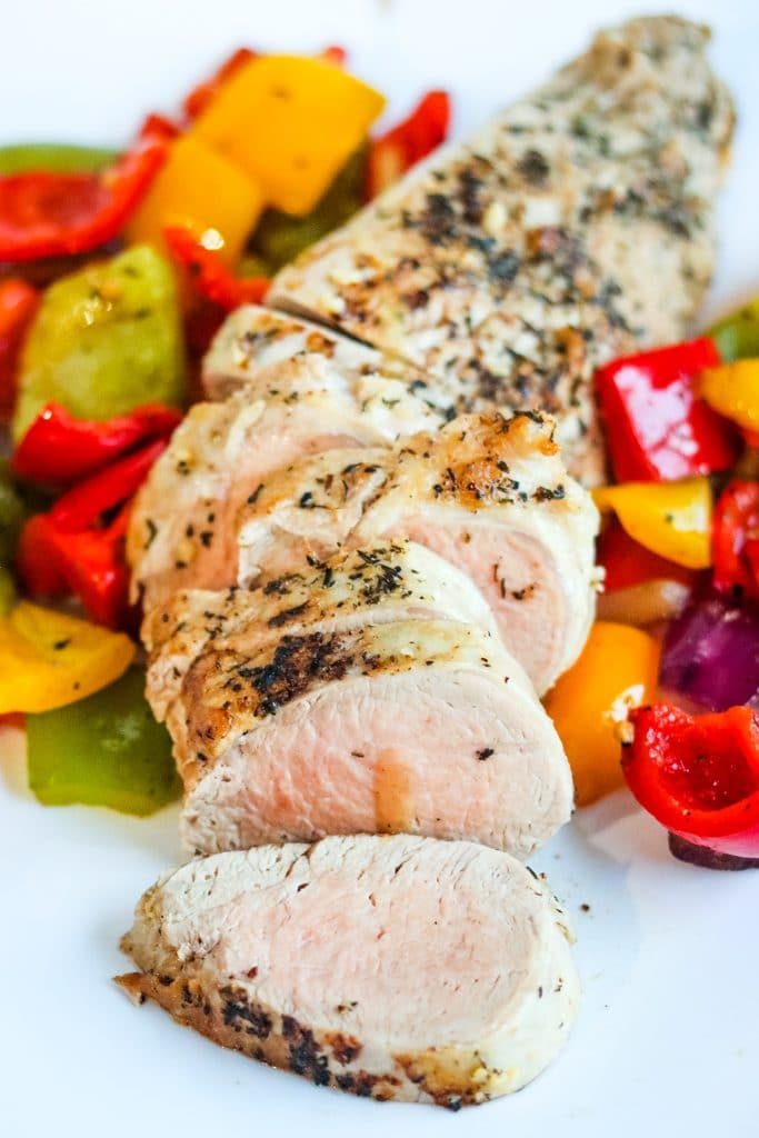 Sliced, pan roasted pork tenderloin with vegetables on white plate.