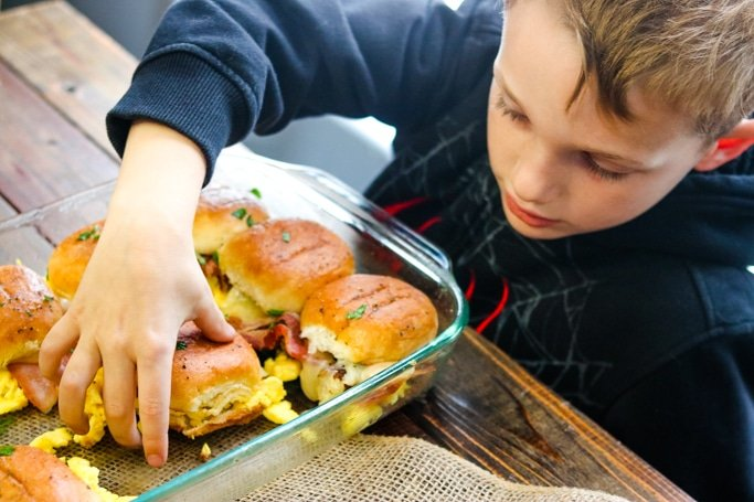 boy grabbing a breakfast slider out of a pan