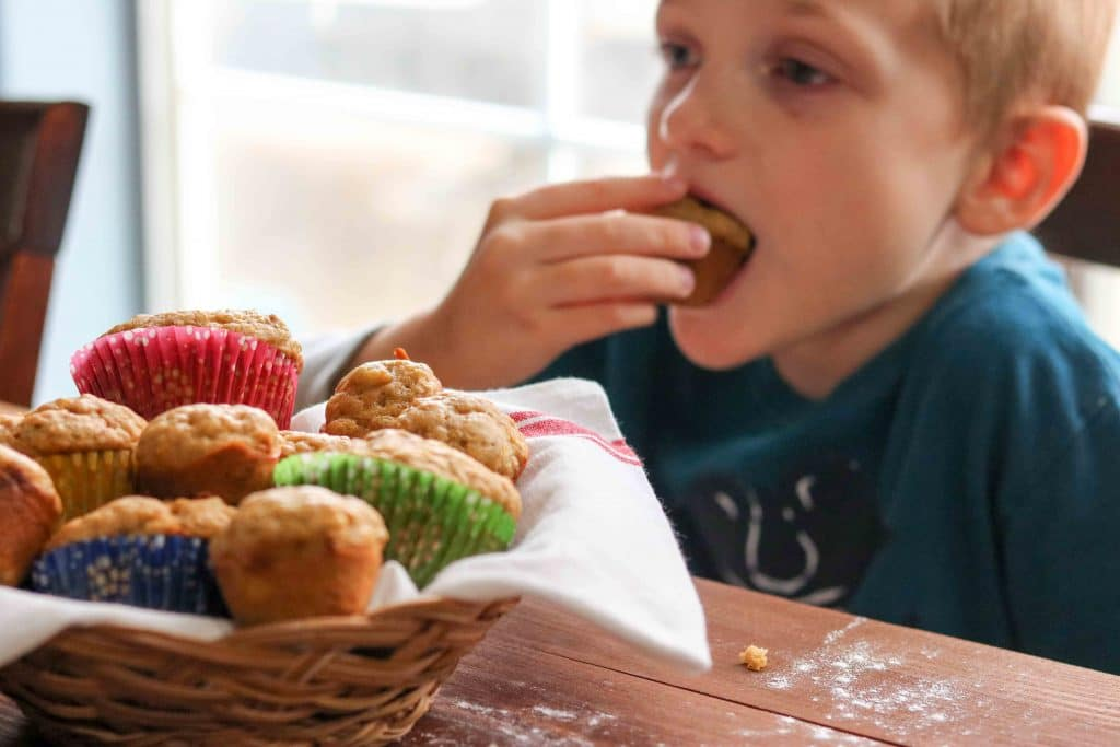 Basket filled with butternut squash muffins and child eating a muffin in background.