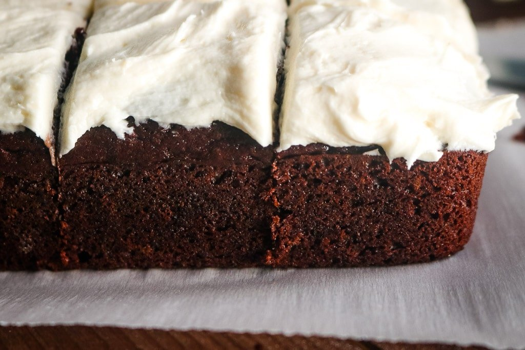 Closeup shot of sliced easy chocolate cake with vanilla buttercream frosting.