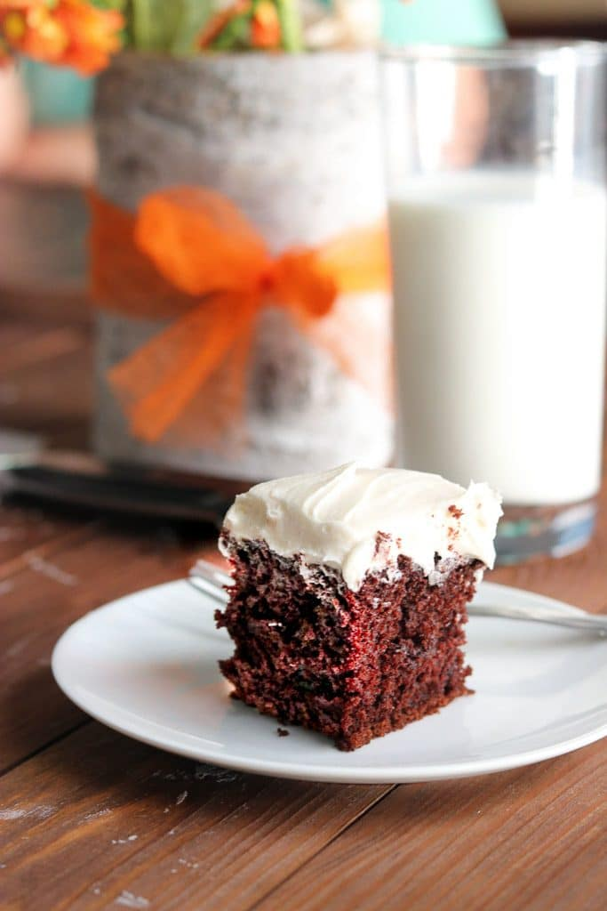 Chocolate cake with vanilla buttercream frosting on white plate with glass of milk on wooden table.