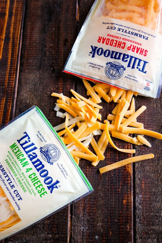 Shot of Tillamook farm shredded cheese on wooden table showing off the large shreds.