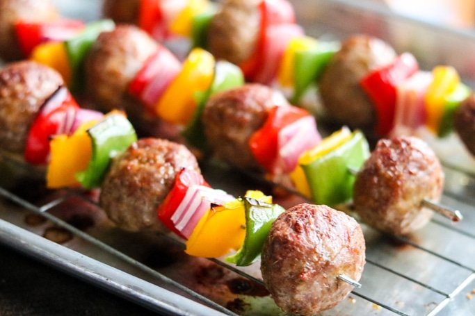 Three Italian meatball kabobs on baking sheet.