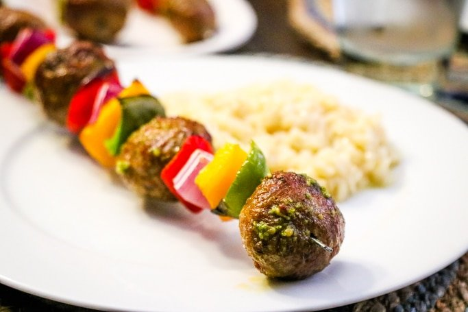 Italian meatball kabobs with rice on white plate.