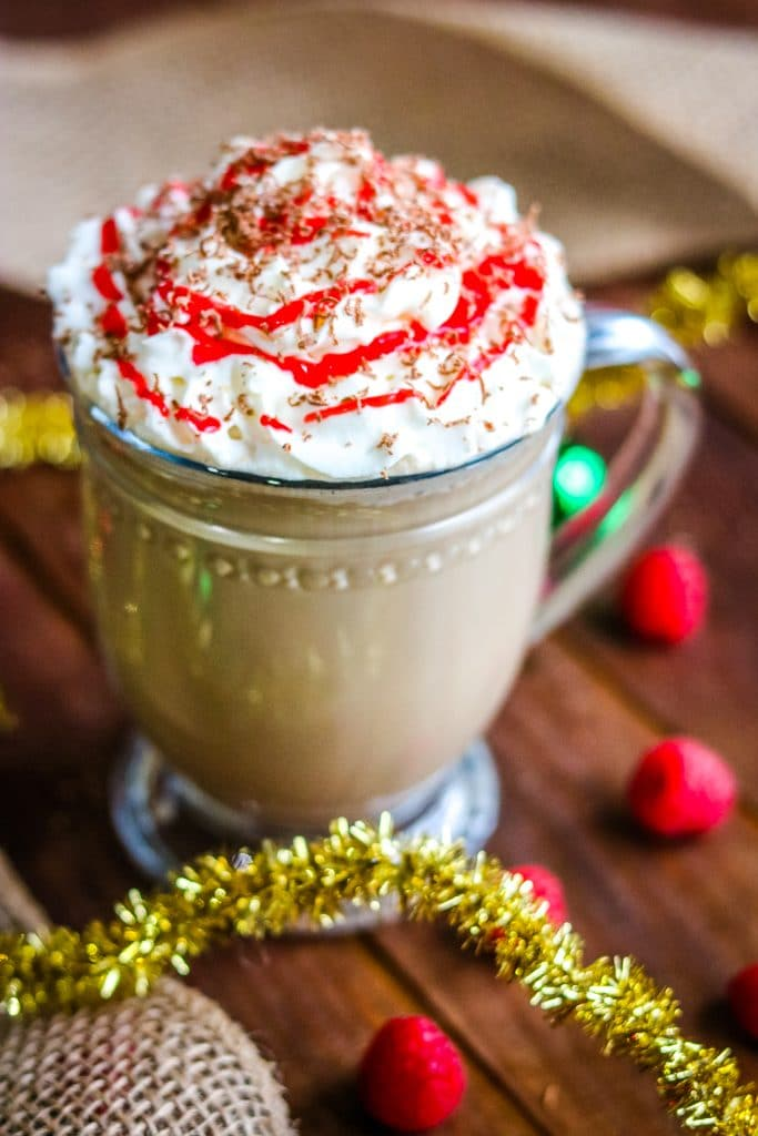 raspberry mocha latte in a glass cup with whipped cream and raspberry topping