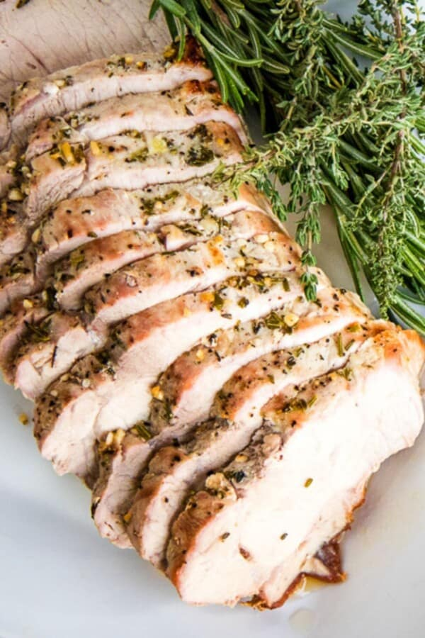 roasted pork loin in slices with sprigs of thyme
