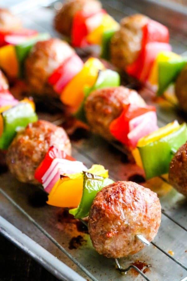 Cooked Italian meatball kabobs on baking sheet.