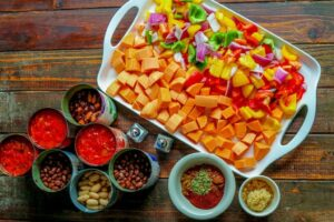 Chopped vegetables on white serving tray and canned ingredients on wooden table.