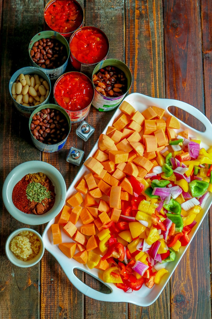 Overhead shot of diced vegetables on white serving tray, canned ingredients, and spices on wooden table.