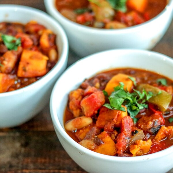 Three bowls of slow cooker vegetarian chili on a wooden table.