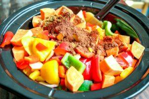 Seasonings added to chopped vegetables in Crockpot.