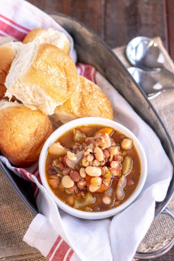 15 bean soup in a white bowl with rolls