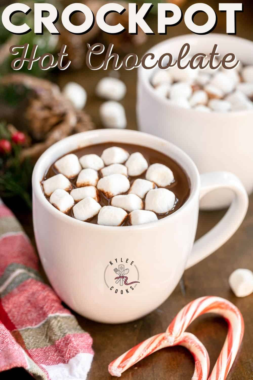 white mug of crockpot hot chocolate with winter decorations with text overlay