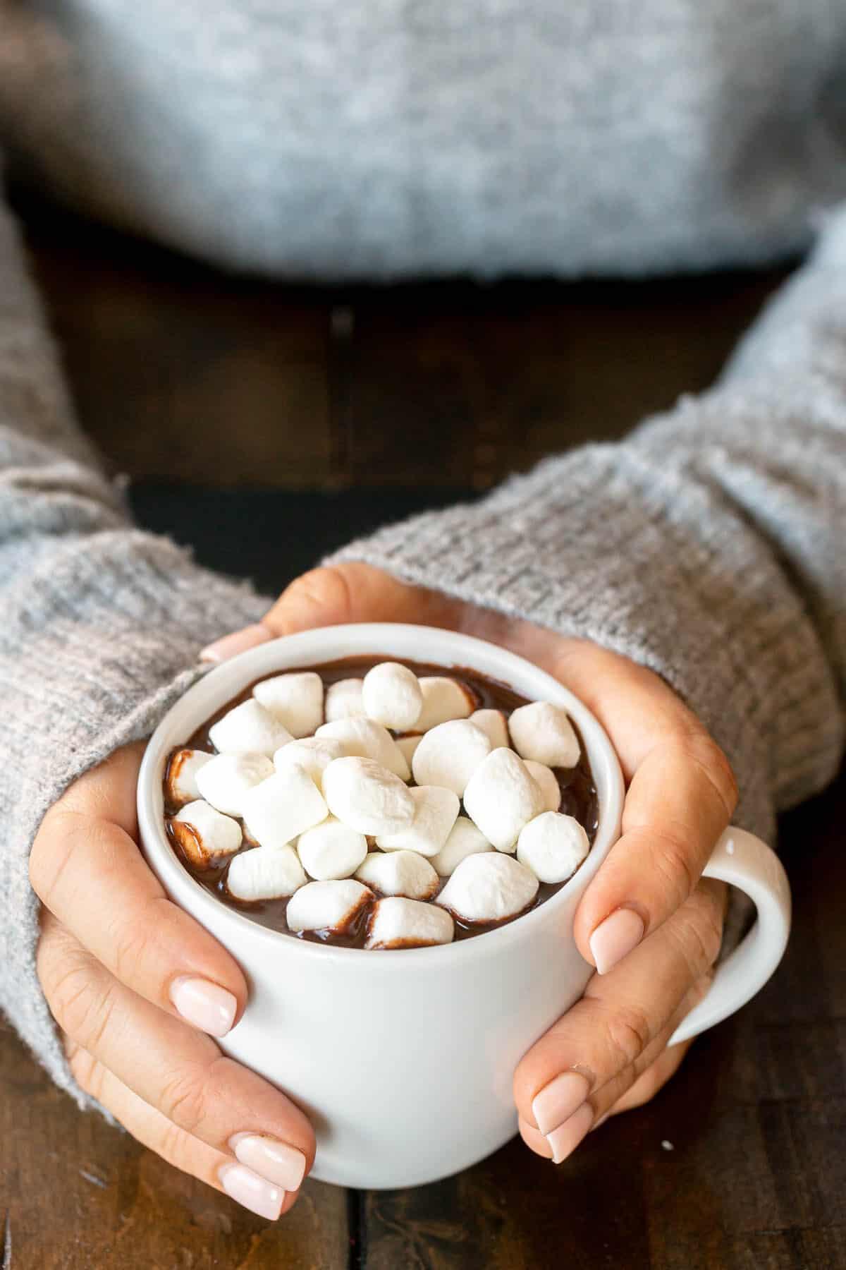 hands around a white mug full of hot chocolate