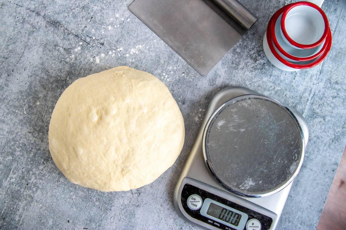 hamburger bun dough next to a food scale