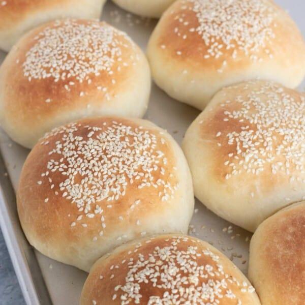 Homemade hamburger buns on a baking sheet