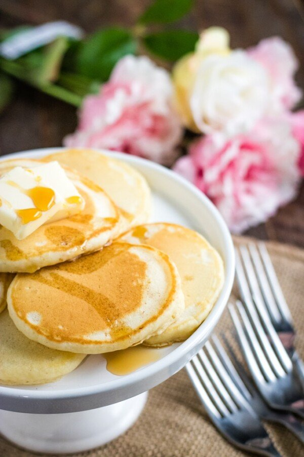 stack of homemade pancakes with forks and pink flowers