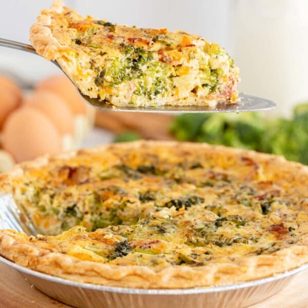 broccoli quiche being lifted out of a pie pan