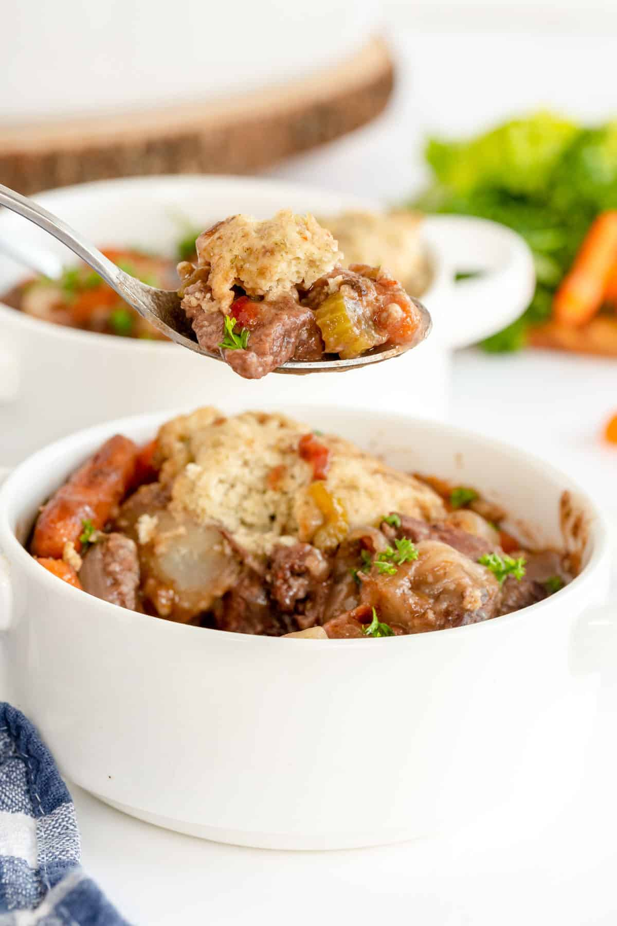 beef stew with dumplings in a white bowl on a spoon