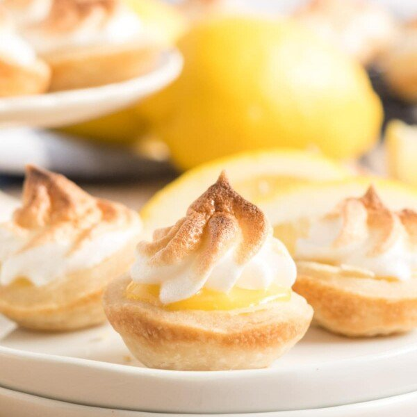 mini lemon meringue pies on a white plate with a lemon
