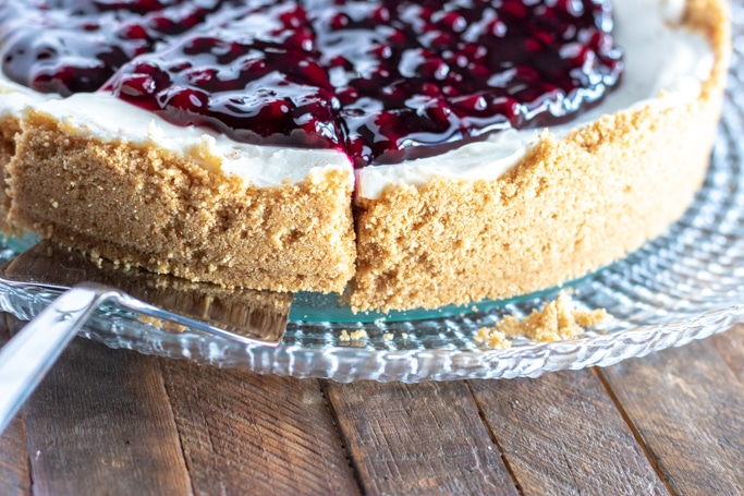 whole blueberry cheesecake on a clear platter with a slice cut out
