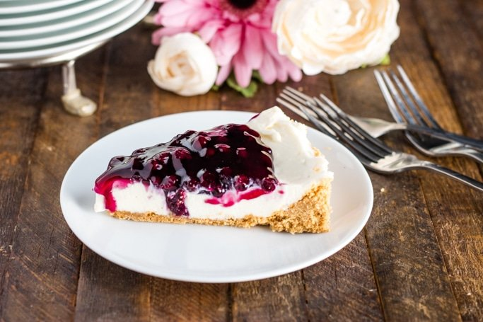 No bake cheesecake on a white plate with forks and pink/white flowers