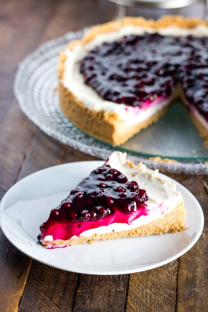 No bake cheesecake on a white plate with a platter of cheesecake