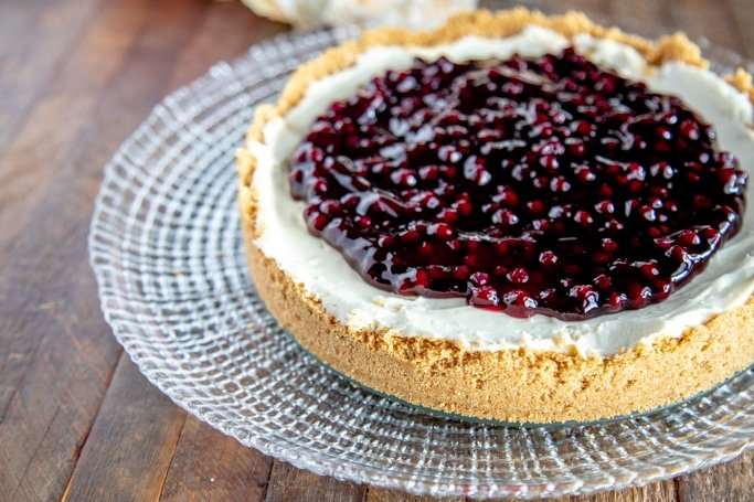 whole blueberry cheesecake on a clear platter