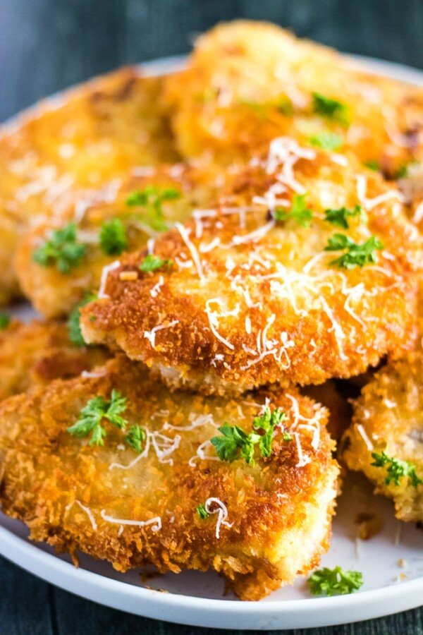 Pork schnitzel on a white plate with parsley and parmesan