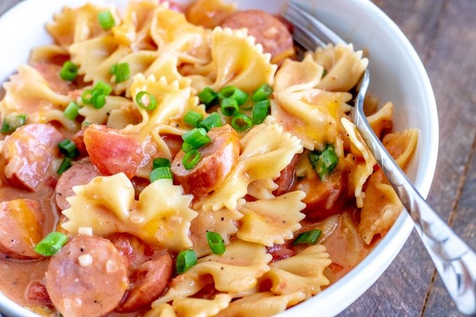 close up of a bowl of sausage pasta with a fork