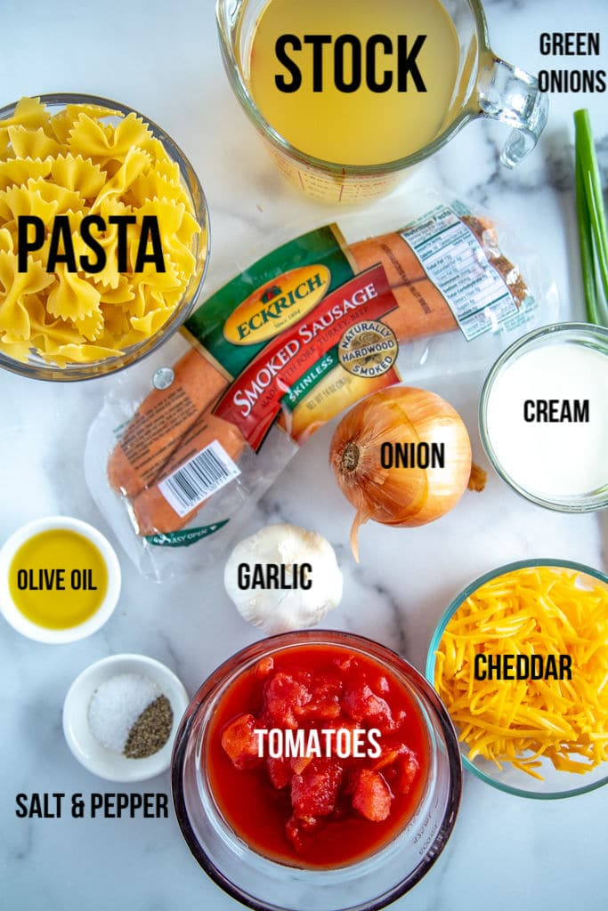 sausage pasta ingredients: pasta, stock, tomatoes, green onions, olive oils, garlic, cream, cheddar