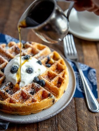 Blueberry waffle with powdered sugar, whipped cream and blueberries with syrup being poured over the top