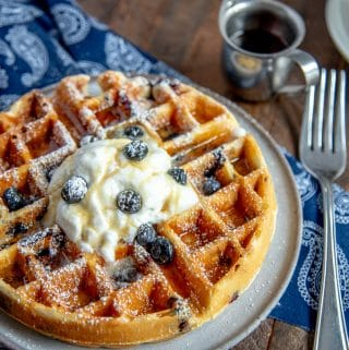 blueberry waffles with whipped cream, powdered sugar, with a fork and maple syrup