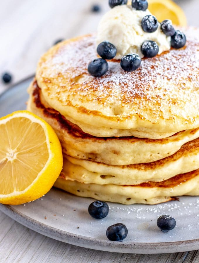 stack of pancakes with a cut lemon, ricotta and blueberries