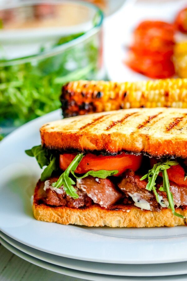 steak sandwich on a plate with grilled corn and salad