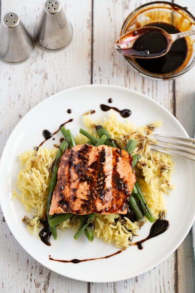 Pan seared salmon on a white plate with green beans and rice, and a balsamic glaze
