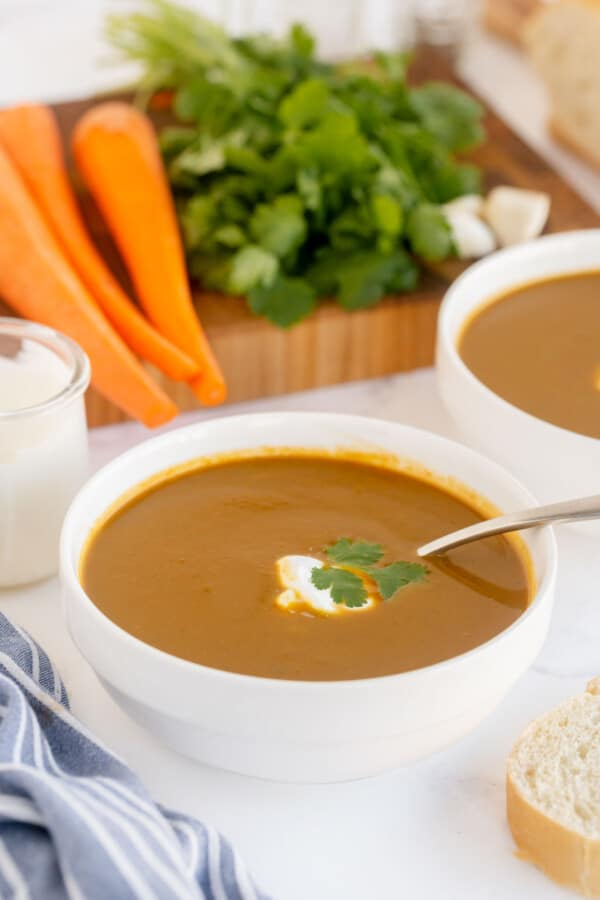carrot soup in a white bowl with veggies in t