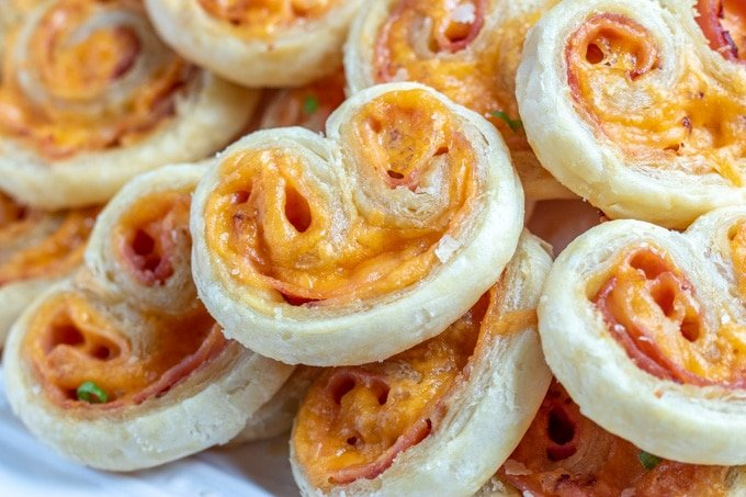 close up of savory ham and cheese palmiers on a platter