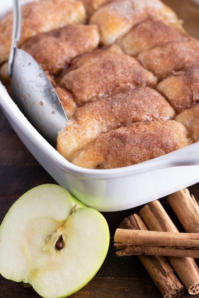 apple dumplings in a white casserole dish with a cut apple and cinnamon sticks