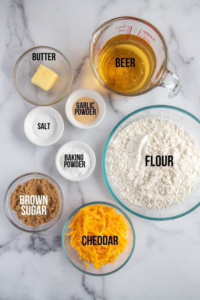 cheddar beer bread ingredients with labels, on a marble counter