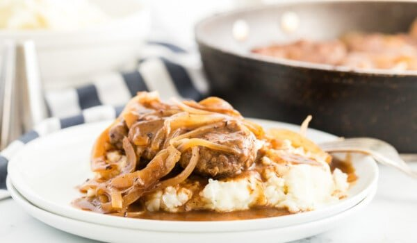 hamburger steaks on a white plate smothered in onions