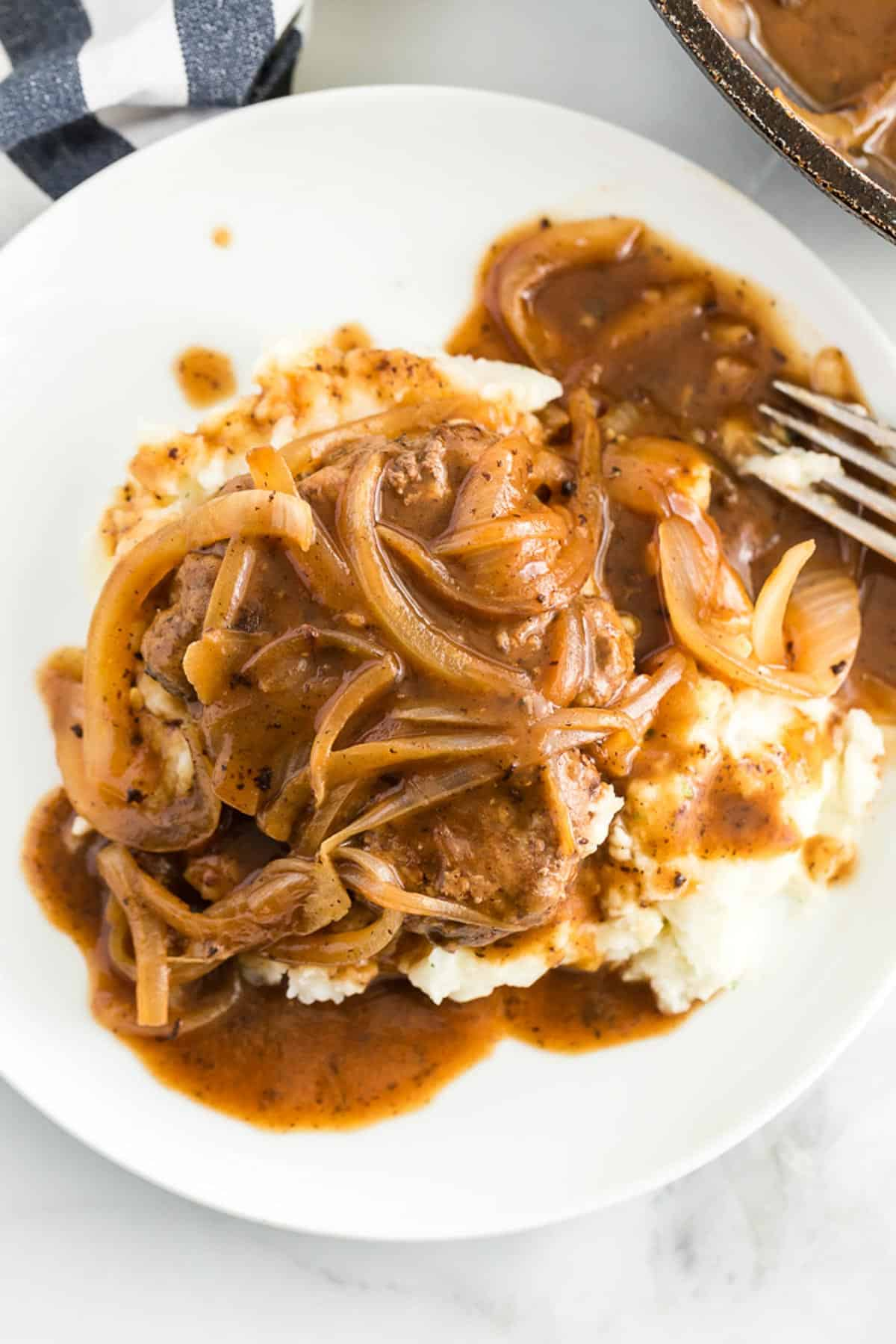 hamburger steak on a white plate smothered in onions