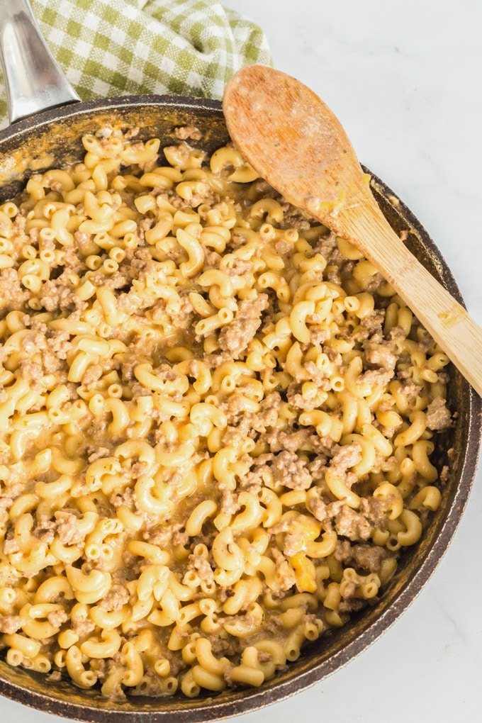 Homemade Hamburger helper (cheeseburger macaroni) in a skillet with a wooden spoon.
