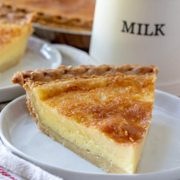 Buttermilk pie on a plate with a milk jug