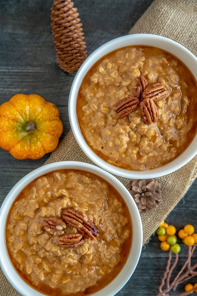 2 white bowls with pumpkin oatmeal decorated with pecans, on a burlap sack