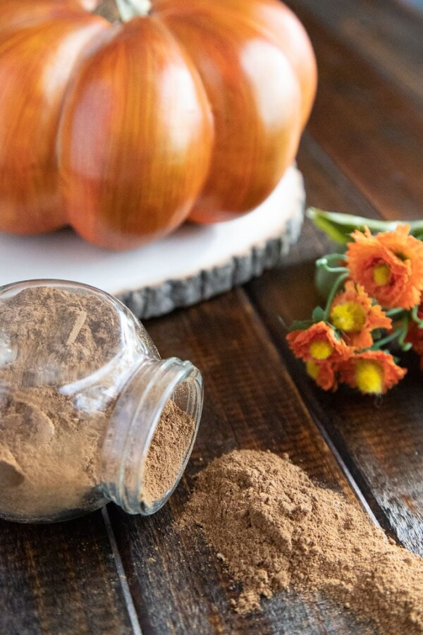 pumpkin pie spice spilling out of a glass jar on a wooden board