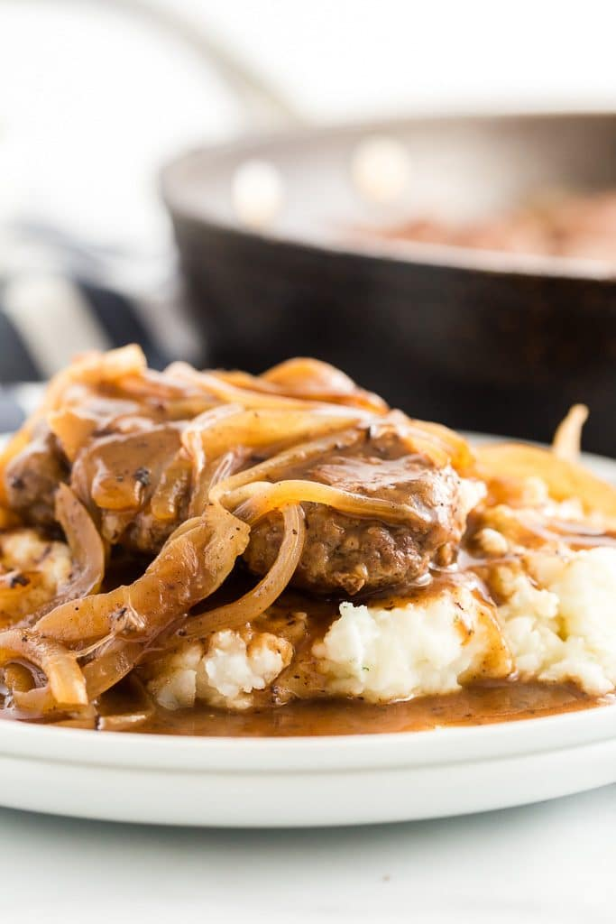 Salisbury steak on a white plate smothered in onions