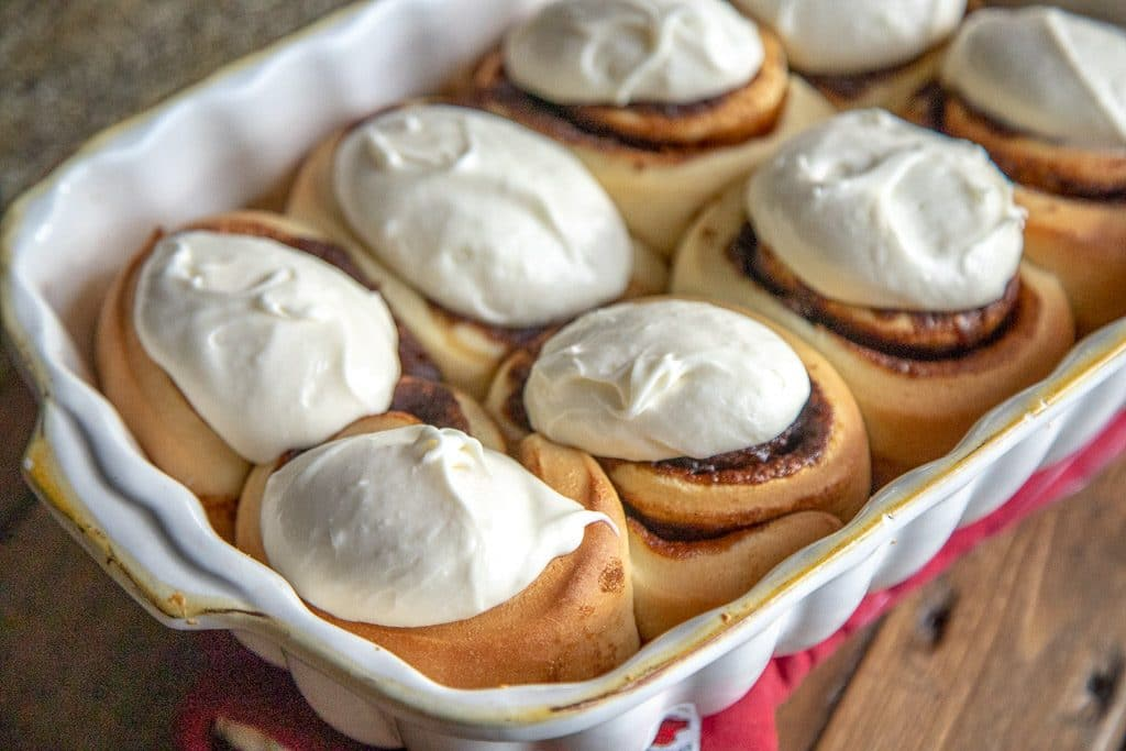 cinnamon rolls with frosting in a white baking dish